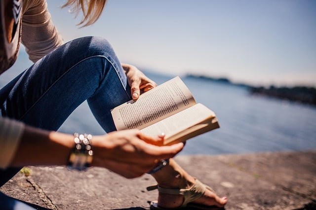 Image of a mom reading outside in the sunshine. Image is placed at the top of an article about self care tips for moms.